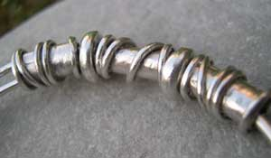 handmade silver beads on an expanding bangle