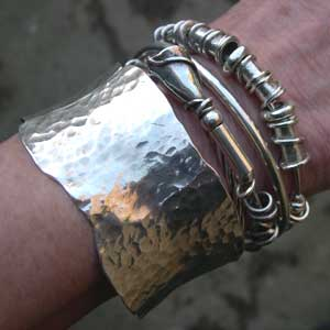 silver expanding bangle being worn with silver cuff