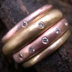 stack of eternity rings in yellow and red gold with diamonds
